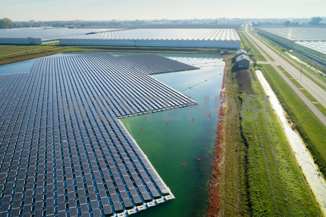 Floating solar panels installed on water supply of neighbouring greenhouses, elevated view, Netherlands - CUF47941