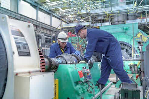 Engineers inspecting gears at generator end in nuclear power station during outage - CUF47953