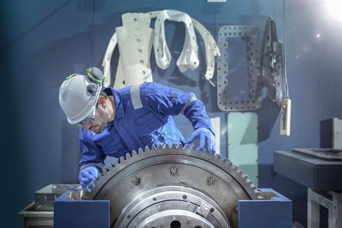 Engineer inspecting large gear during outage in nuclear power station - CUF47962