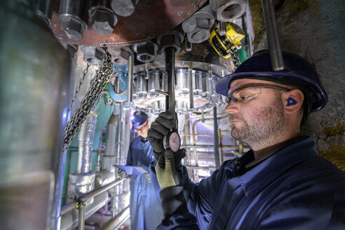 Engineer working in confined space under turbine during outage in nuclear power station - CUF47965