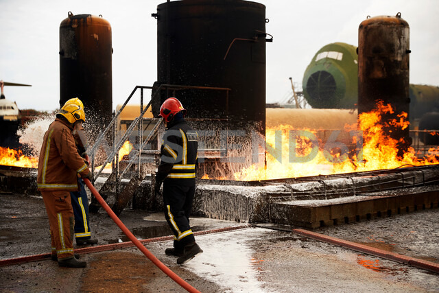 Firemen training, spraying firefighting foam onto oil storage tank fire at training facility - CUF47980