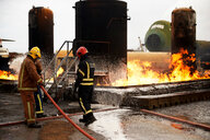 Firemen training, spraying firefighting foam onto oil storage tank fire at training facility - CUF47980