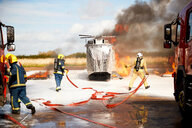 Firemen training, team of firemen extinguishing mock helicopter fire at training facility - CUF47983