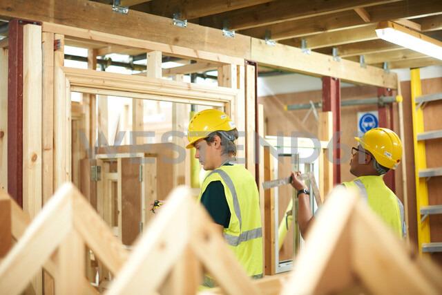 Male higher education students building wooden framework in college workshop - CUF48007