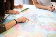 College students studying world map in classroom - CUF48013