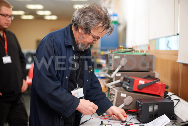 Lecturer preparing electrical instrument, student in background - CUF48016
