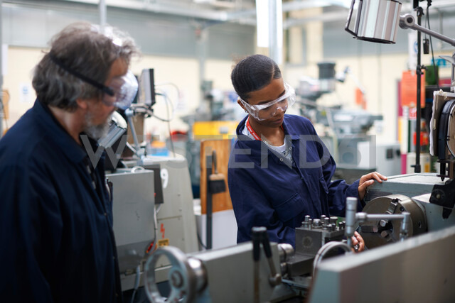 Lecturer teaching student to operate machine in workshop - CUF48019
