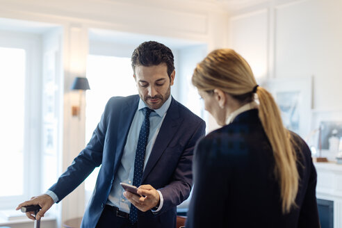 Businessmen showing text message to colleague in office - CUF48055