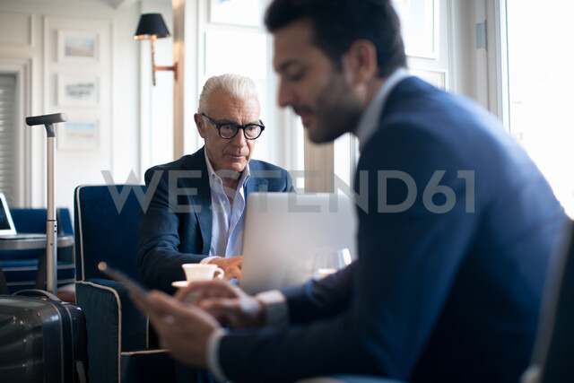 Businessmen using digital tablet and laptop in office - CUF48061 - Sofie Delauw/Westend61