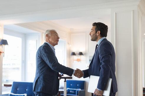Businessmen shaking hands in office - CUF48064
