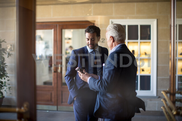 Businessman showing text message to colleague in front of office - CUF48067