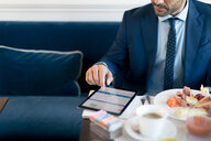 Businessman using digital tablet in restaurant - CUF48070