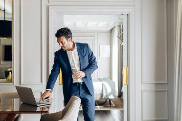 Businessman using laptop in suite - CUF48073