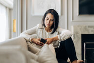 Businesswoman using smartphone in suite - CUF48076
