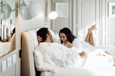 Couple laughing and relaxing in suite - CUF48079