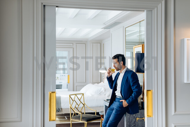 Businessman with iced drink, deep in thoughts in suite - CUF48082 - Sofie Delauw/Westend61