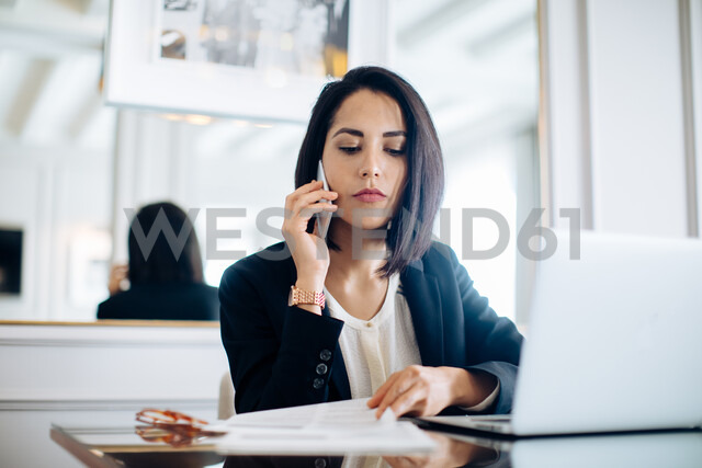 Businesswoman using smartphone and laptop in suite - CUF48085
