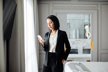 Businesswoman using smartphone in suite - CUF48088