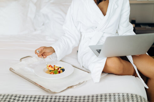Woman using laptop and having breakfast in suite - CUF48091