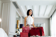 Fashionable woman with shopping bags in suite - CUF48094