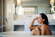 Woman relaxing in bathtub in suite - CUF48097