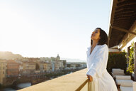Woman enjoying sun on hotel balcony, Florence, Toscana, Italy - CUF48100