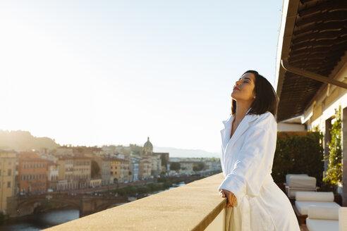 Woman enjoying sun on hotel balcony, Florence, Toscana, Italy - CUF48100