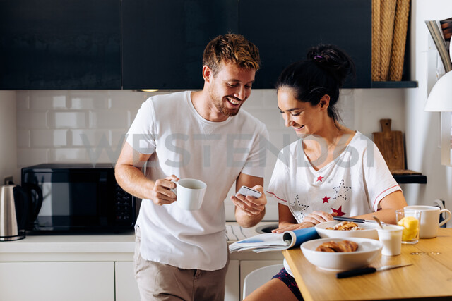 Young couple using smartphone in kitchen - CUF48106