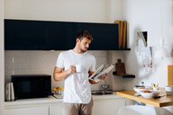 Young man reading magazine in kitchen - CUF48109