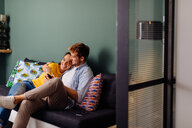Young couple hugging on couch - CUF48121