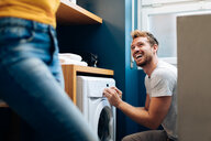 Young man operating washing machine at home - CUF48127