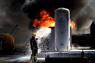 Fireman training to put out fire on burning tanks, Darlington, UK - CUF48145