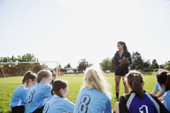 Coach talking to middle school girl soccer team on sunny field - HEROF05249