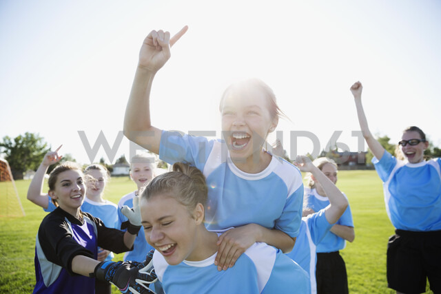 Exuberant middle school girl soccer team celebrating and cheering on sunny field - HEROF05255 - Hero Images/Westend61