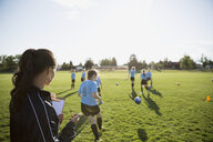 Coach watching and timing middle school girl soccer team running drills at practice on sunny field - HEROF05258