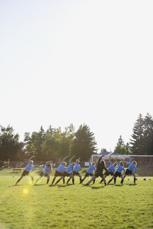 Coach and middle school girl soccer team stretching at practice on sunny field - HEROF05261