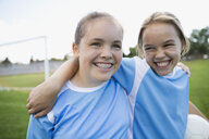 Enthusiastic middle school girl soccer teammates hugging on field - HEROF05267