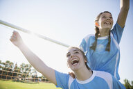 Exuberant middle school girl soccer teammates celebrating and cheering on sunny field - HEROF05270