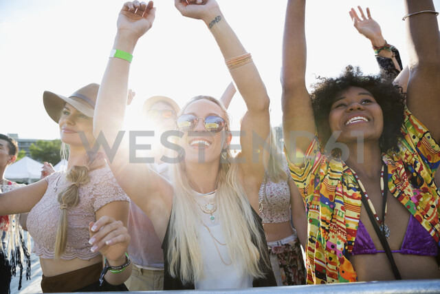 Enthusiastic young women cheering in crowd at summer music festival - HEROF05276