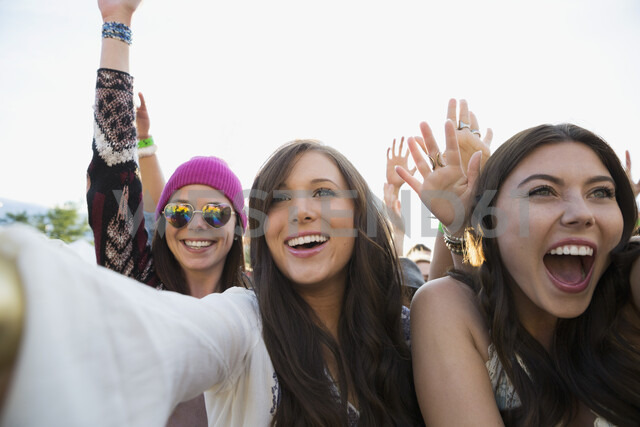 Enthusiastic young women cheering in crowd at summer music festival - HEROF05279 - Hero Images/Westend61