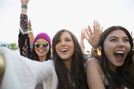 Enthusiastic young women cheering in crowd at summer music festival - HEROF05279