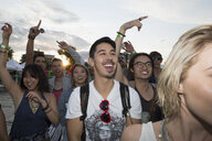 Enthusiastic young man in crowd at summer music festival - HEROF05285
