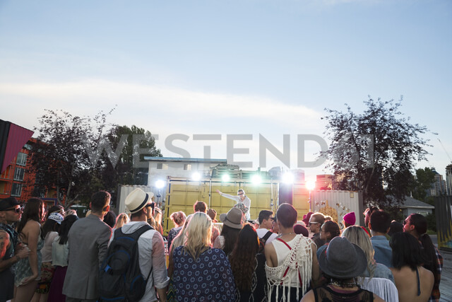 Crowd watching musician on illuminated stage at summer music festival - HEROF05288