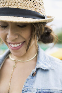 Close up portrait smiling young woman wearing necklace and straw hat looking down - HEROF05300