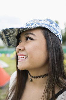 Close up portrait smiling young woman wearing baseball hat looking away - HEROF05303