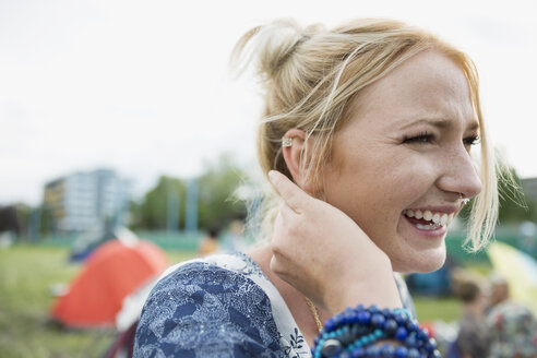 Close up portrait laughing young blonde woman looking away at summer music festival campsite - HEROF05306