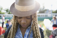 Close up portrait young woman with blonde braids wearing hat looking down at summer music festival campsite - HEROF05312