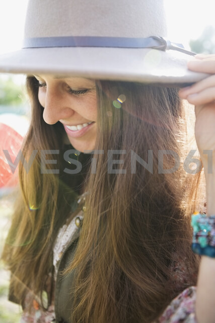 Close up portrait smiling young brunette woman wearing hat looking down - HEROF05315
