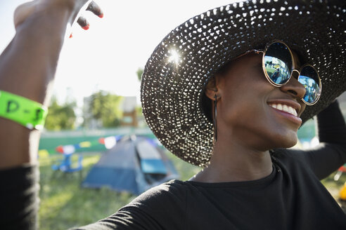 Close up portrait smiling young woman wearing hat and sunglasses dancing at summer music festival campsite - HEROF05324