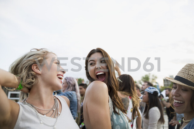 Enthusiastic young women dancing in crowd at summer music festival - HEROF05333